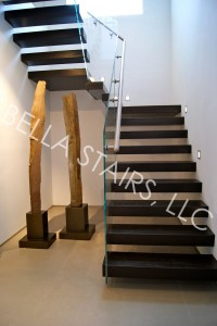 After: Cantilevered wood staircase with glass railing and a stainless steel handrail.